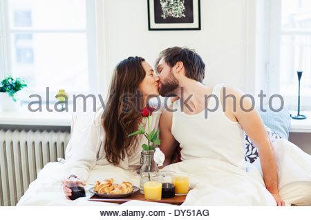 Junges Paar küssen, frühstücken im Bett - Stockfoto