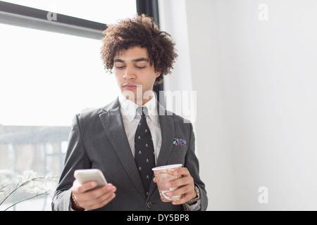 Junger Mann mit Handy mit Kaffee - Stockfoto