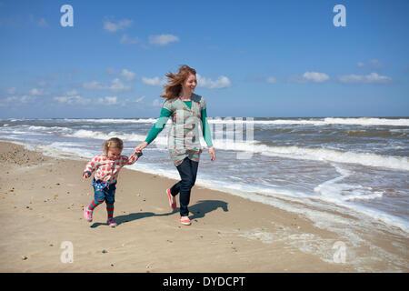 Eine Mutter und Tochter läuft am Horsey Strand an der Küste von Norfolk. - Stockfoto