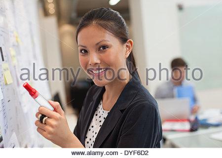 lächelnde Geschäftsfrau vorderen Whiteboard im Büro - Stockfoto