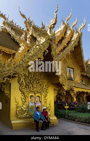 Touristen sitzen vor dem vergoldeten WC-Haus am Wat Rong Khun, weiße Tempel, von dem Architekten Chalermchai Kositpipat - Stockfoto