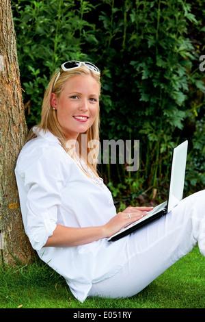 Eine junge Frau mit einem Laptop im Garten sitzt und surft im Internet. WLAN in den Park, Eine Junge Frau Sitzt - Stockfoto