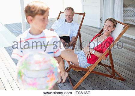 Eltern, die gerade Sohn mit Ball auf Deck spielen - Stockfoto