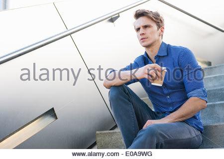 Mitte erwachsener Mann eine Kaffee-Pause auf Stadt-Schritte - Stockfoto