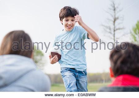 Eltern, die gerade Sohn mit Rugby-Ball im Park laufen - Stockfoto