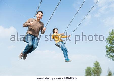 Vater und Sohn Spaß auf Park-Schaukel - Stockfoto