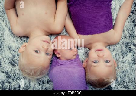 Geschwister auf Teppich liegend - Stockfoto