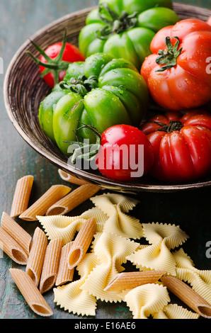 Frische grüne und rote Tomaten mit gemischten Teigwaren - Stockfoto