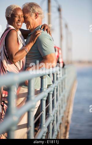 Älteres paar umarmt am pier - Stockfoto
