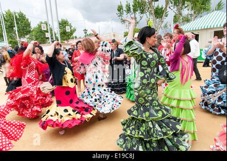 Frauen in bunten Flamenco-Kleider tanzen auf der Sevilla April Messe, Spanien - Stockfoto