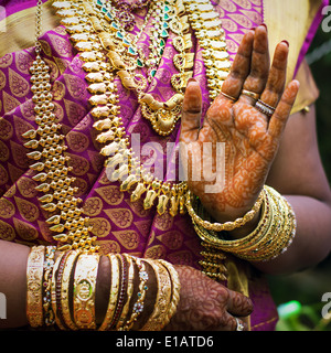 Eine indische Braut mit Schmuck, Armreifen geschmückt und mit Henna bemalt - Stockfoto