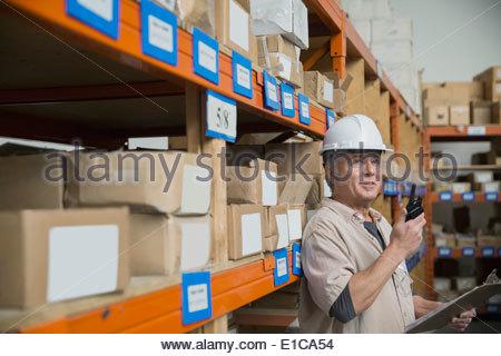 Arbeiter mit Walkie-talkie im Lager - Stockfoto