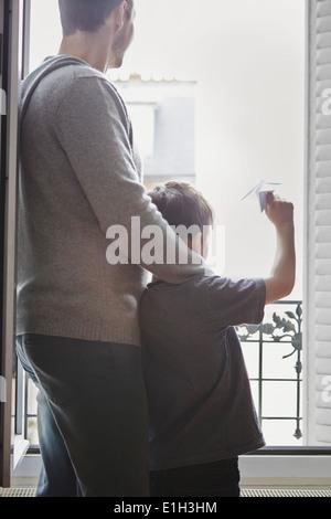 Junge Papierflieger aus Fenster starten - Stockfoto