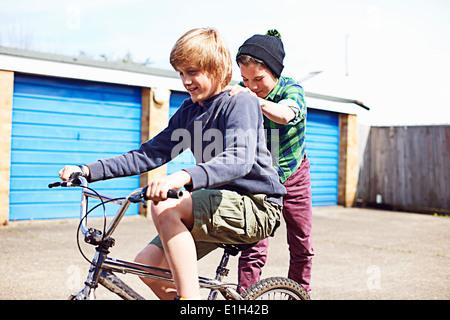 Junge Freund geben eine Fahrt auf Rückseite Fahrrad - Stockfoto