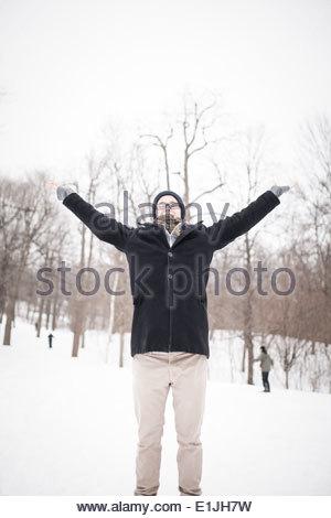 Junger Mann stehend im Park mit erhobenen Armen - Stockfoto