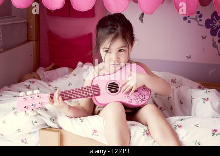 Kleines Mädchen sitzt auf dem Bett, Spielzeug Gitarre spielen - Stockfoto