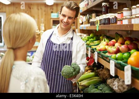 Assistent hilft Kunden bei Gemüsetheke Hofladen - Stockfoto