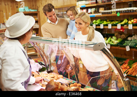 Sales Assistentin serviert Familie In Feinkost - Stockfoto