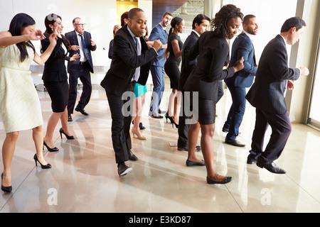 Unternehmer und Unternehmerinnen im Büro Lobby tanzen - Stockfoto