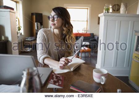 Frau in Fachzeitschrift am Esstisch - Stockfoto