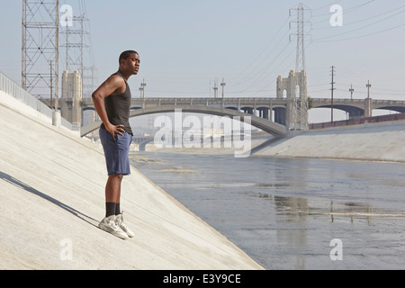Junge männliche Läufer eine Pause am Ufer der Stadt - Stockfoto