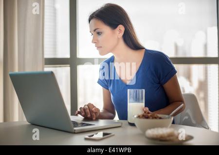 Junge Frau mit Laptop, während beim Frühstück - Stockfoto
