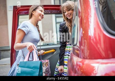 Junge Frauen ins Taxi, Einkaufstaschen tragen - Stockfoto