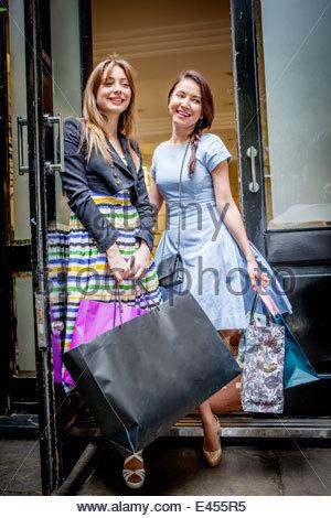 Junge Frauen, die Einkaufstaschen tragen - Stockfoto