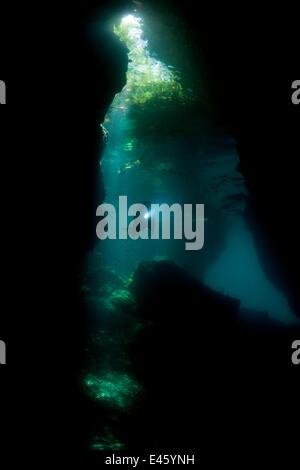 Licht-streaming in eine flache Höhle in einem Tauchplatz namens The Passage, mit einem Taucher schwimmen durch. - Stockfoto