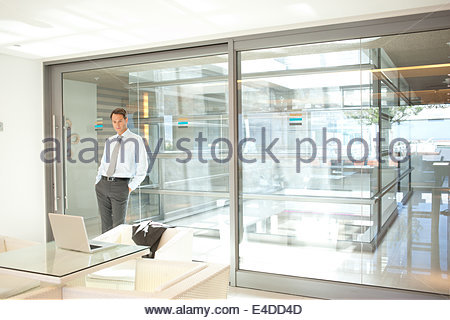 Geschäftsmann gelehnt Glaswand im Büro - Stockfoto