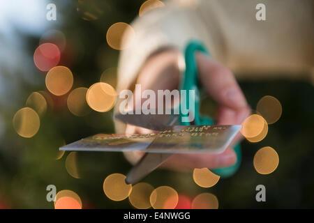Studioaufnahme von weiblicher Hand schneiden Kreditkarte mit einer Schere - Stockfoto