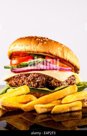 Frische Hamburger mit Gemüse und Pommes Frites auf reflektieren Hintergrund - Stockfoto