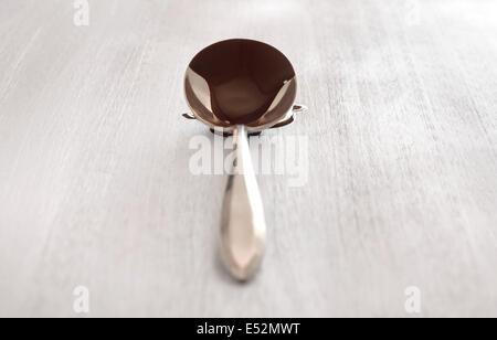 Antike Löffel gefüllt mit Schokolade. Schokolade tropft auf weißen Holzoberfläche. Helle, saubere Einstellung. - Stockfoto