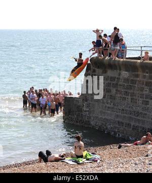 Brighton, Sussex, UK. 18. Juli 2014. Ein junger Mann springt von einer Buhne auf Brighton Beach in einem Kajak als - Stockfoto