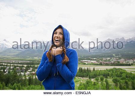 Lächelnde Frau in hoody in der Nähe von Bergen - Stockfoto