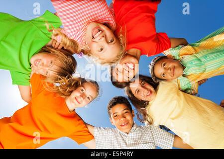 Glückliche Kinder in der Nähe im Kreis am Himmelshintergrund - Stockfoto