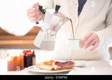 Beschnitten, junge Frau gießt Kaffee zum Frühstück - Stockfoto
