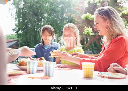 Mutter dient Geburtstagskuchen, Familie auf Geburtstagsparty - Stockfoto