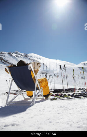 Rückansicht des Mitte erwachsenen männlichen Skifahrer sitzen auf Liegestuhl, Österreich - Stockfoto