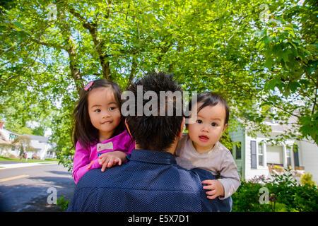 Porträt der Mitte adult Vater mit Baby junge und Mädchen Kleinkind über Schulter - Stockfoto