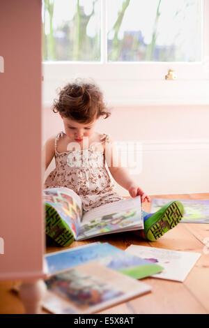 Weiblichen Kleinkind lesen Märchenbücher im Schlafzimmer - Stockfoto