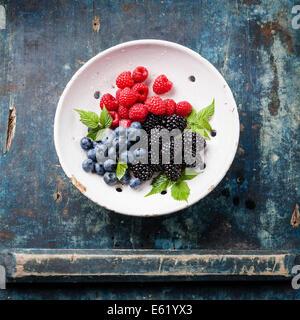 Mischung aus frischen Beeren mit Blätter in Vintage Keramik Sieb auf blauem Hintergrund aus Holz - Stockfoto