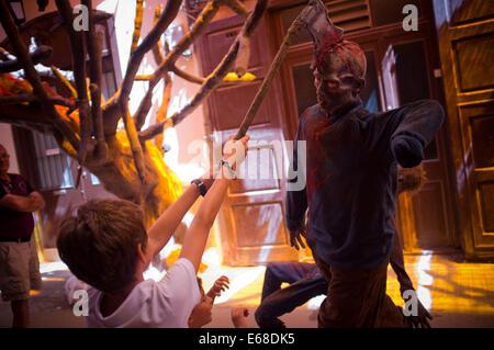 Barcelona, Spanien. 18. August 2014. Kinder spielen mit einer Axt auf den Kopf eines Zombies in Gracia Viertel von - Stockfoto