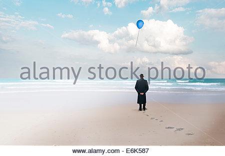 Mann komponieren mit Mantel und Hut stehen am Strand, auf der Suche nach einem Ballon - Stockfoto