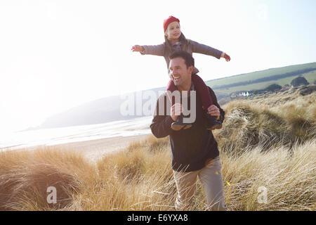 Vater und Tochter zu Fuß durch die Dünen am Strand von Winter - Stockfoto