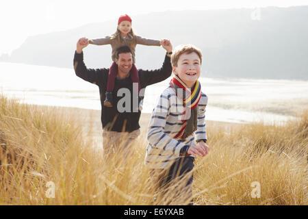 Vater und Kinder zu Fuß durch die Dünen am Strand von Winter - Stockfoto