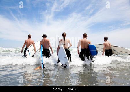 Rückansicht einer Gruppe von männlichen und weiblichen Surfer Freunde waten in Meer mit Surfbrettern - Stockfoto