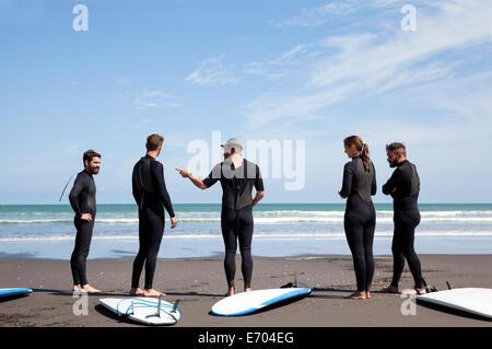 Gruppe von männlichen und weiblichen Surfer-Freunde im Chat am Strand - Stockfoto