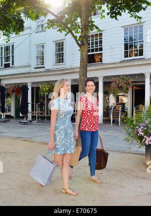 Zwei junge Frauen, die ein Spaziergang entlang der Straße Einkaufstaschen tragen - Stockfoto