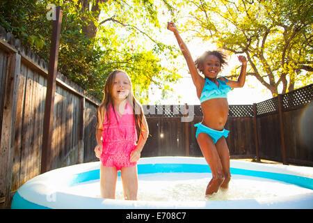 Zwei Mädchen im Garten Planschbecken springen - Stockfoto